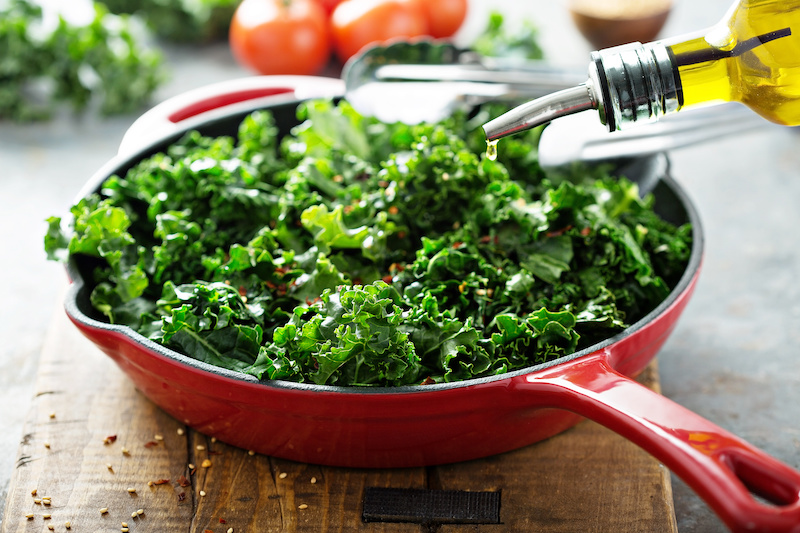 Foods That Can Help Relieve Your Chronic Pain; Quickly sauteed kale with chili flakes in a cast iron pan with olive oil pouring over, healthy cooking concept