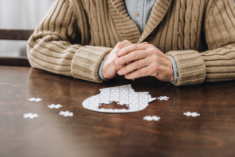 Can Dementia Be Prevented? ; cropped view of retired man playing with puzzles on table