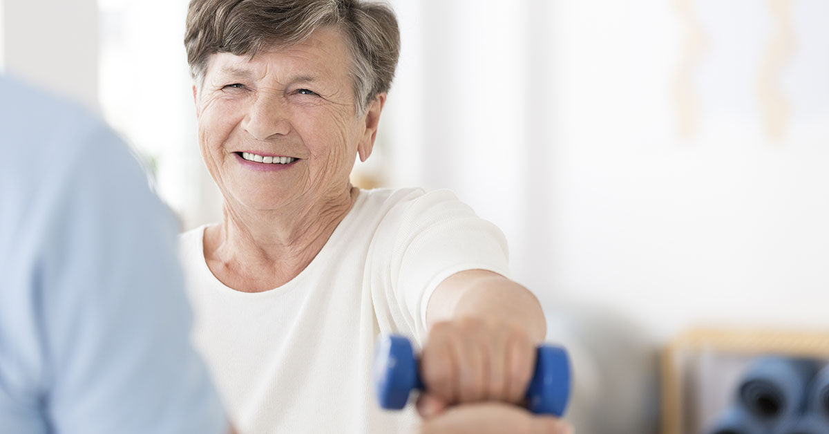 Happy senior woman exercising arms with small weights with help from a physiotherapist; blog: What You Need to Know About Stroke Recovery